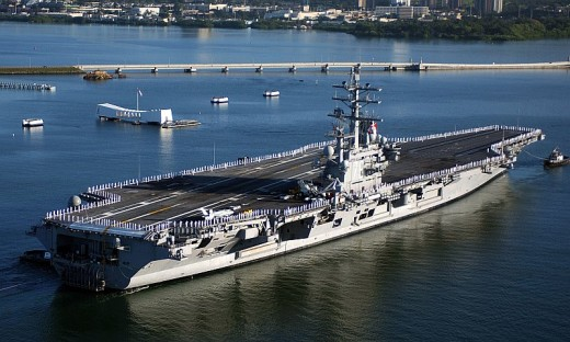 USS Ronald Reagan (CVN-76) sailors man the rails and render honors to the USS Arizona Memorial.