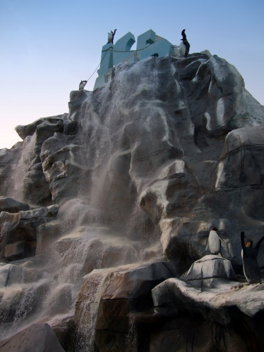 The entrance to Iceland Waterpark has a huge waterfall coming down a large rock face.