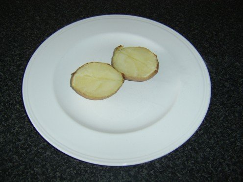 The cooked potato is halved lengthwise
