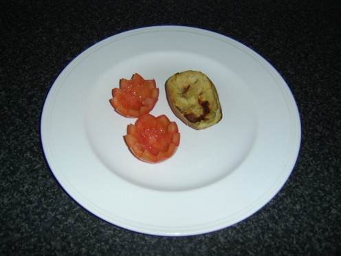 Crispy potato skin and scooped out tomato halves are plated