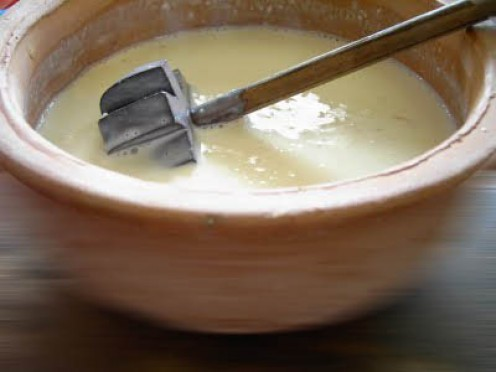 churning the cream with a hand churn