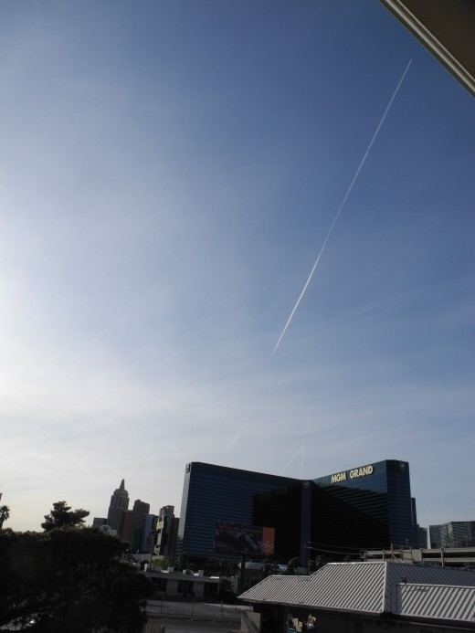 The MGM Grande Hotel shortly before sunset.  Milky Opaque sky that has been receiving Chemtrail after Chemtrail for hours to build a density BEFORE this last Chemtrail crosses the sky for its film debut and portrait.
