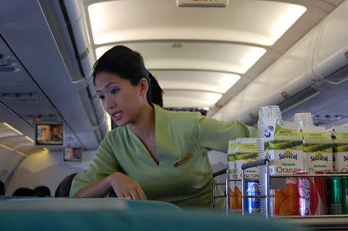 A flight attendant conversing with passengers while serving beverages.