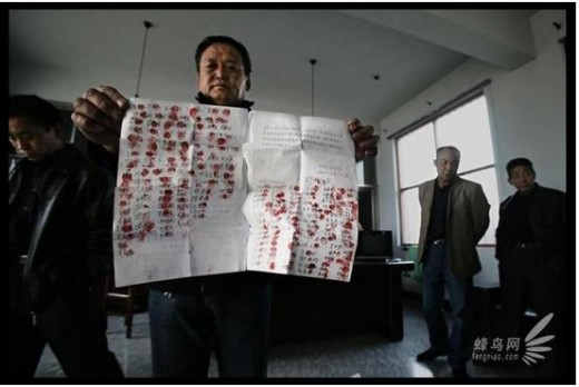 Villagers present demands for change and a petition for damages due to pollution to Party officials. They have signed with their fingerprints.