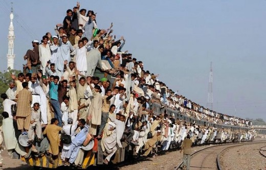 train travel in india with people hanging onto the sides