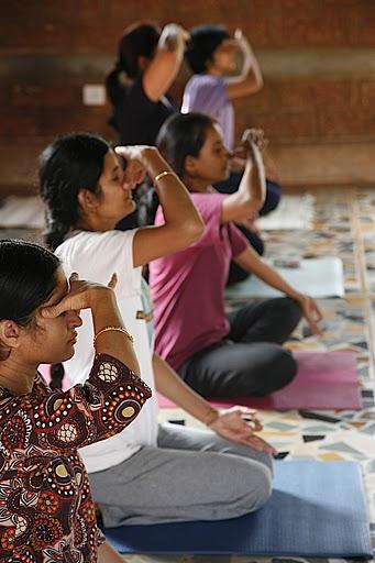 Women performing pranayama during a yoga class.