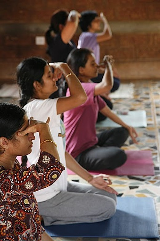 Women performing pranayama during a yoga class.