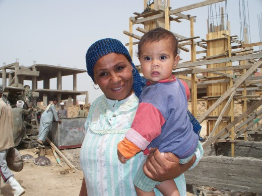 Mother and her child walking by a construction site in Dahab, Egypt