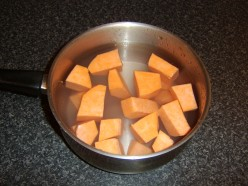 Sweet potatoes are chopped and added to a pot of cold water