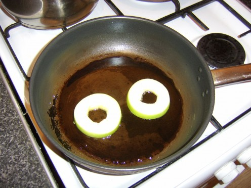 Cored apple slices are added to a frying pan containing hot honey