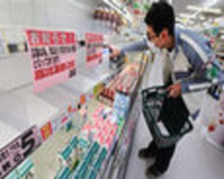 The photo is fuzzy but the man grocery shopping is wearing a surgical mask.