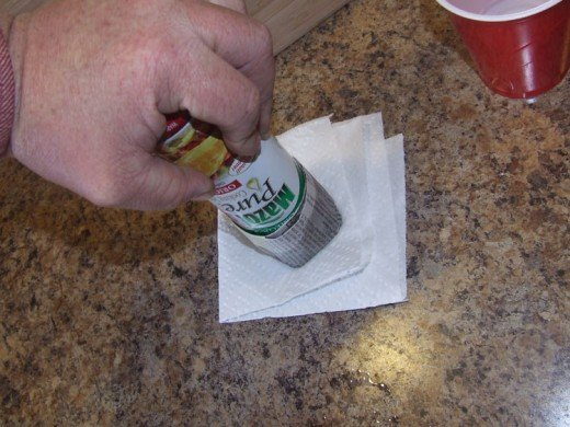 Here I have folded a paper towel twice, creating 4 layers. Press the wet end into the paper towel firmly, creasing the folds on the bottom of the pot. Feel free to twist the lid of the can down and into the folds, back and forth a few turns