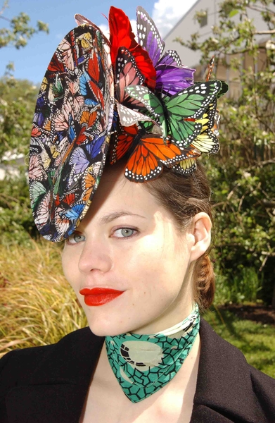 A clutch of colourful butterflies resting on a models head. Hat by Philip Treacy