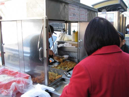 A food cart on Mott Street and Canal Street serving a small container of fried noodles for $1.50