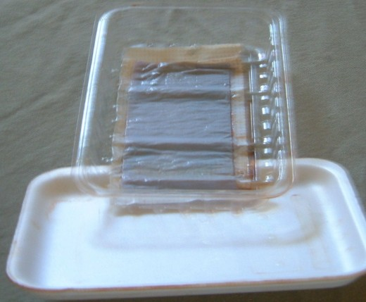 Plastic Lid, Styrofoam and then wrapped in plastic wrap. This held beef liver.