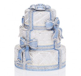 "Limited edition, triple tiered wedding cake minaudire with enamel bow accents, top snap closure and 19"" chain. Comes lined in an exclusive blue satin."