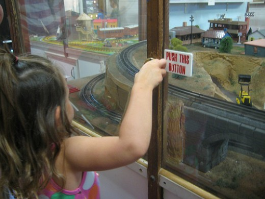 Here in this picture a girl is pushing the button to experience the the real sound a real train makes.