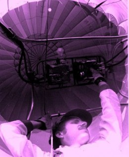 An unusual angle of a hot air balloonist checking his equipment.