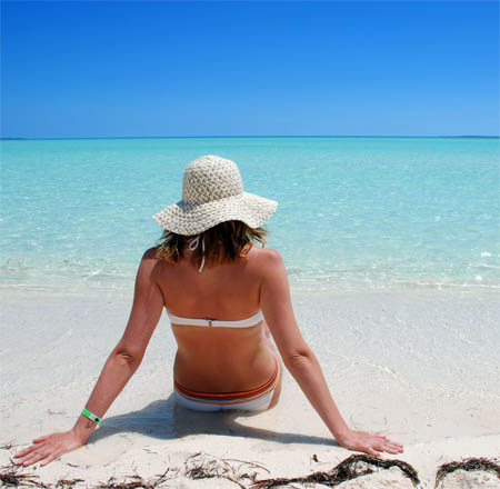 protect your skin while at the beach with hat and sunscreen