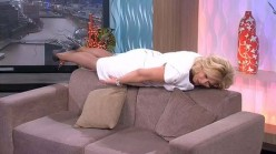 An Australian TV host engagng in a low level  plank.