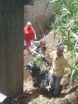 Carlos/Charlie (native from the city drug rehabilitated with the help of the ministry) Laura, and Donna hauling bamboo dirt and rocks.