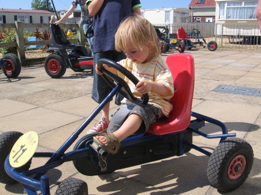 Sitting on a go-kart - this is a still image, little children can't pedal these themselves and so need to be a passenger on a multiple seat kart.