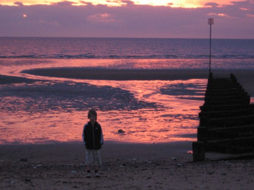 My son, standing on the beach.