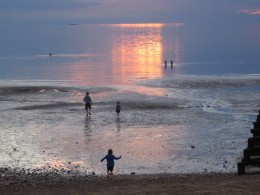 Children messing about on the shore as the sun goes down.