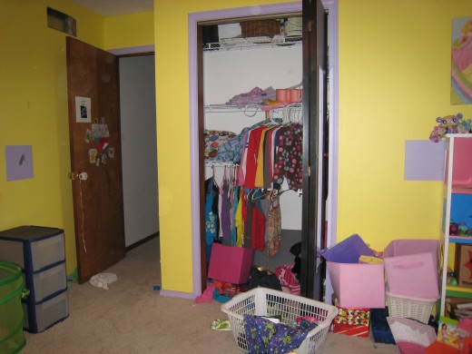 The floor of her closet is completely covered with...well junk.