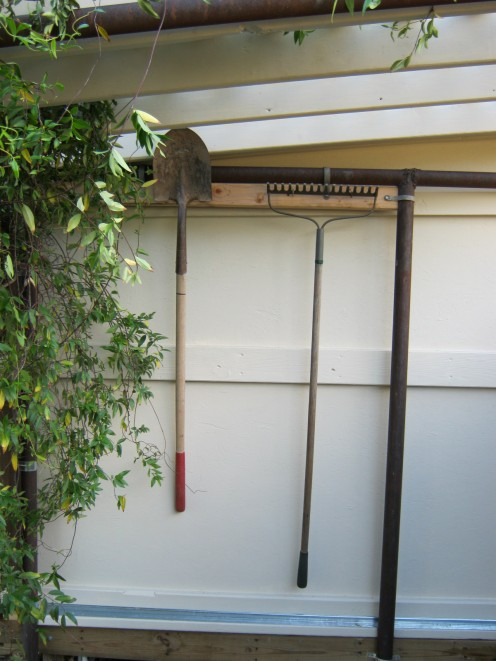 Tool hanger with tools under pergola.