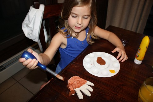 Child painting her hand.