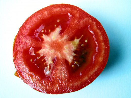 Squeeze tomatoes to remove the pulp and seeds.