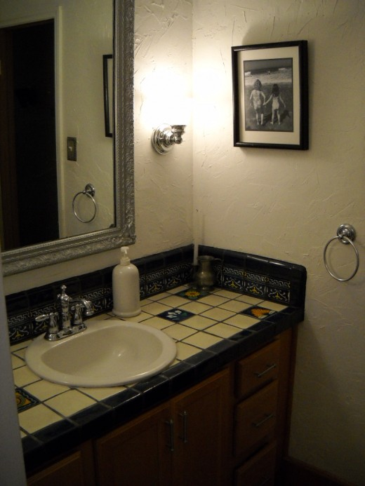 Classic white and blue mexican tile countertop with chrome accents and black and white photos.