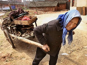 """An elderly Chinese woman collects scraps of wood for cooking, near the Yangtze river city of Jiujiang."" (Mark Ralston/AFP/Getty Images)"