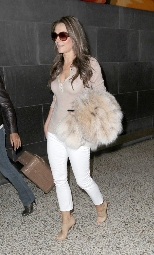 Elizabeth Hurley in skinny white jeans and high heels.
