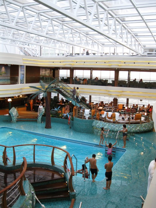 People enjoying the indoor swimming pool area on the cruise ship Splendida