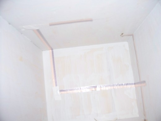 I run the tape through the middle of each whole drawn on the wall.  Make as few turns as possible.  Where there is a turn in the wire tape, put electrical tape over the turn.
