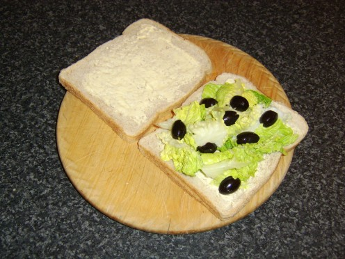 Lettuce and black olives are placed on the bread first