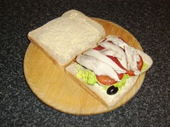 Chicken and tomato are laid on top of the lettuce