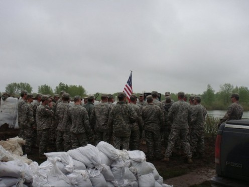 Members of the ND National Guard take a break from fighting the flood to hold a Memorial Day Service in a resident's backyard.
