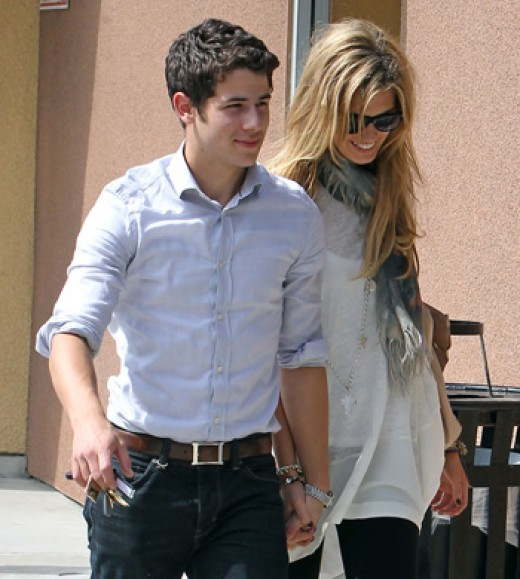 Nick Jonas and Delta Goodrem holding hands outside of a Studio City, California Starbucks.