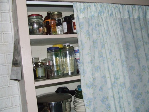 A simple tension curtain rod and an old sheet can hide a multitude of sins.