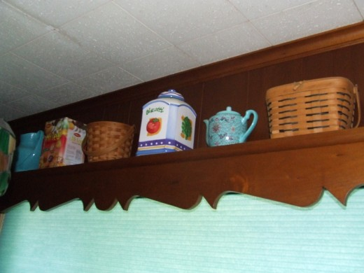 I kept the cornice that was above the window from the '70's.  It saved me money because I didn't have to buy a curtain. Then I stored items that we only use once in a while on top.  (Don't they look pretty?)