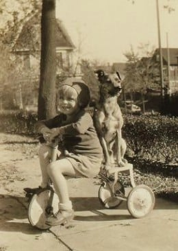 Riding her bike with family dog Jiggs.