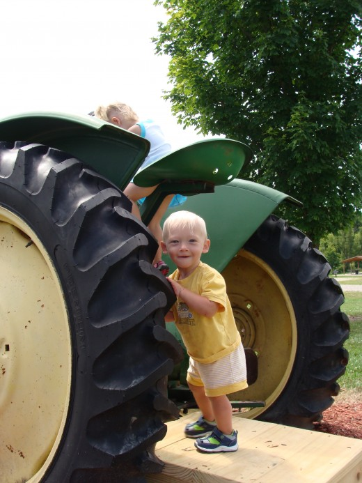The birthday boy next to a John Deere tractor.