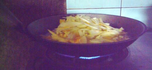 Cook the papaya in coconut milk under medium fire. (Photo by Travel Man)