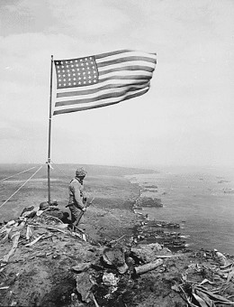 From the crest of Mount Suribachi, the Stars and Stripes wave in triumph over Iwo Jima after U.S. Marines had fought their way inch by inch up its steep lava-encrusted slopes., ca. 02/1945