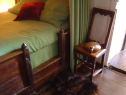 Easy access to the bed and a chair designed to warm your back in front of the fire