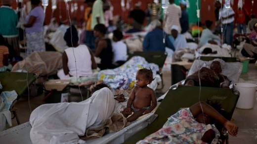 A baby sits next to her mother who suffers from cholera symptoms in a sport center that has been converted into a cholera treatment center in Cap Haitien, Haiti, Tuesday Nov. 23, 2010. (AP / Emilio Morenatti)