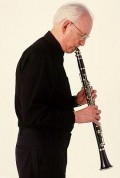 You hold a clarinet with two hands, left above right.  You change notes by pressing fingers over holes or against metal keys.